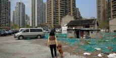 Les carnets de commande restent trop vides,  la chute parait très probable pour le secteur des services chinois. (Photo : Une femme promène son chien dans le quartier abandonné de Guangfuli, à Shanghai, en Chine, le 8 avril 2016.)