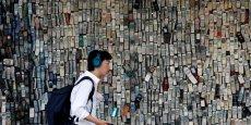 Un homme utilisant un smartphone passe devant un mur de magasin électronique décoré d'anciens téléphones cellulaires.