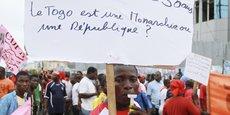 Un homme tient une pancarte lors d'une marche contre un troisième mandat pour le président sortant Faure Gnassingbe à Lomé le 12 décembre 2014.