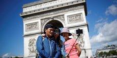 Des touristes prennent un selfie devant l'Arc de Triomphe sur l'avenue des Champs Elysées, en France, le 3 août 2017.