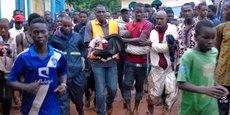 Les secouristes, composés de bénévoles, de membres de la Croix-Rouge, transportent le corps d'une fillette survivante après le drame.