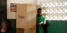 Un jeune libérien prépare son bulletin de vote lors des élections présidentielles dans un bureau de vote à Monrovia, le 26 décembre 2017.