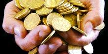 Un homme tient une poignée de pièces dorées australiennes dans ses mains. Argent. Money.