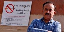 S.K. Arora, chef de l'administration du tabac du gouvernement de Delhi, pose un photogrhe à côté d'un panneau anti-tabac collé sur un mur de l'école à côté d'une route à New Delhi, en Inde, le 13 avril 2017