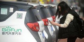 Grâce à l'application de son téléphone, une femme peut régler la location et l'utilisation immédiate d'une voiture électrique de la marque Gofun dans un parc proposant un service de voitures partagées de la ville de Yangzhou.