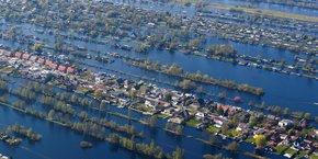 Aux Pays-Bas, les habitants ont l'habitude de vivre entourés d'eau comme dans ces maisons bâties dans les environs d'Amsterdam (vue aérienne du 20 avril 2018). Mais ce mode de vie est menacé par l'élévation continue du niveau des océans, comme par l'intensification des épisodes de tempêtes.