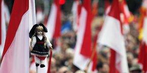 Une poupée vêtue d'un costume traditionnel alsacien est suspendue à un drapeau lors d'une manifestation pour protester contre le projet d'unification des régions d'Alsace, de Lorraine et de Champagne-Ardenne.
