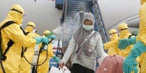 Des médecins diffusent un spray antiseptique sur une femme rapatriée de Chine en Indonésie, le 2 février 2020.
