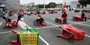 Des clients attendent leur tour devant une grande surface à Chatsworth près de Durban le 31 mars 2020, deux jours après le début de la période de 21 jours de confinement décrétée par les autorités de Pretoria.
