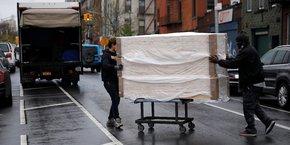 Des employés déplacent une pile de nouveaux cercueils d'un entrepôt vers un camion de livraison, le 24 avril 2020, dans le quartier de Brooklyn, à New York, extrêmement touchée par la pandémie de coronavirus (COVID-19).