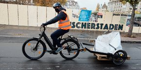 Les livreurs strasbourgeois transportent les pavés à l'aide d'un vélo électrique, équipé d'une remorque.