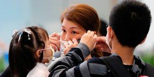 Femme ajuste masque pour prévenir déclenchement nouveau coronavirus Chine