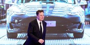 Elon Musk, patron de Tesla, devant un écran montrant une Tesla Model 3, lors de la cérémonie d'ouverture du programme Model Y de Tesla en Chine à Shanghai
