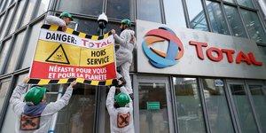 Des militants d'Attac accrochent une bannière à la façade de l'immeuble Total