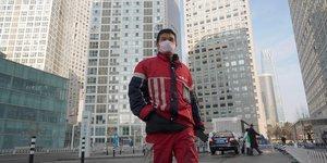 Coronavirus / Covid-19 : un livreur KFC marche dans un complexe commercial situé dans le quartier des affaires de Beijing en Chine
