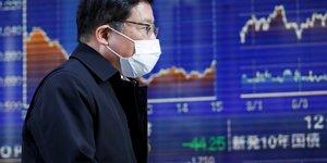 Bourse : un homme portant un masque passe devant un tableau électronique montrant des graphiques de récents mouvements de l'indice Nikkei