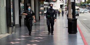 Coronavirus : des officiers du Los Angeles Police Department  (LAPD) portent un masque, alors qu'ils patrouillent sur le Hollywood Boulevard, à Los Angeles, en Californie