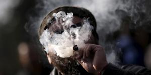 Un homme fume de la marijuana (ou cannabis) lors d'une manifestation en faveur de la légalisation de la drogue