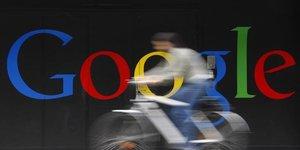 Un employé monte son vélo devant un logo à côté de l'entrée principale de l'édifice Google à Zurich le 9 juillet 2009.