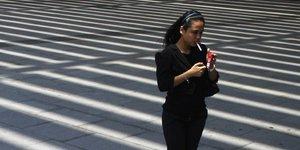 Une femme fume en marchant