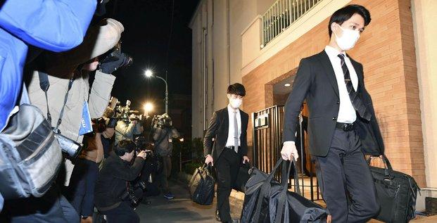 Des agents du bureau du procureur du district de Tokyo portent des sacs après s'être rendus dans la résidence de l'ancien patron de l'alliance Renault-Nissan, à Tokyo