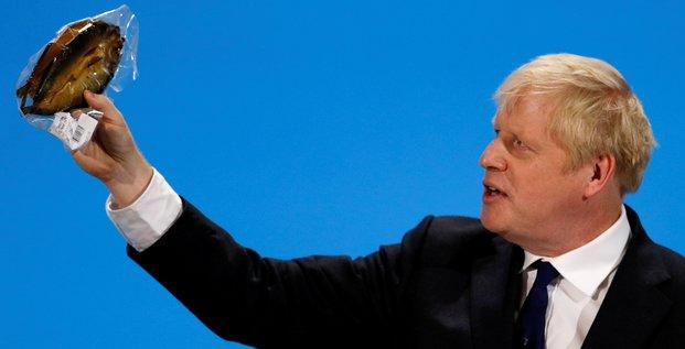 Boris Johnson, alors favori pour le poste de Premier ministre, brandit un hareng fumé dans un emballage plastique à Londres, le 17 juillet 2019. Il accuse la réglementation européenne de nuire aux producteurs de hareng fumé.