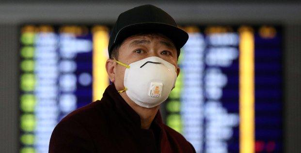 Coronavirus / Covid-19 : Un passager porte un masque tandis qu'il marche dans l'aéroport international de Hong Kong, le 7 février 2020