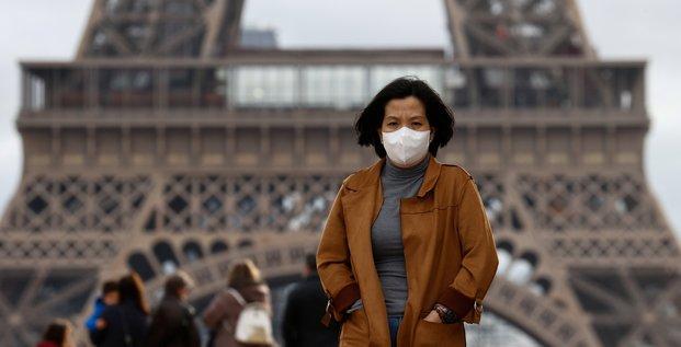 Coronavirus/Covid-19 : Une femme portant un masque marche sur l'esplanade du Trocadéro, devant la Tour Eiffel