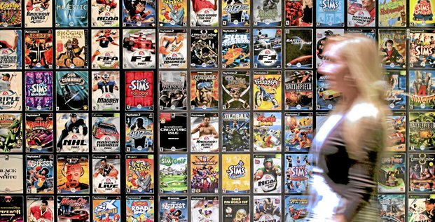 A worker walks past cases for various Electronic Arts Inc. video games at the company's headquarters in Redwood City, California, U.S., on Tuesday, July 20, 2010. Electronic Arts, the world's second-biggest video-game publisher, is in the middle of a market shift, moving away from its declining cons