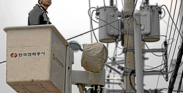 An employee of Korea Electric Power Corporation (KEPCO) works on electric wires in Seoul, South Korea, on Friday, Feb. 9, 2007. Korea Electric Power Corp., South Korea's biggest electricity producer, fell to the lowest in more than 2 1/2 years in Seoul trading after the government said it may cut ta