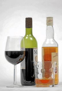 A bottle of Red wine sits next to a bottle of Whiskey in a studio in Kings Lynn, Norfolk, U.K., on Thursday, March 6, 2008. Chancellor of the Exchequer Alistair Darling will announce measures in his budget to make utilities cut bills for Britain's poorest consumers and give companies tax incentives