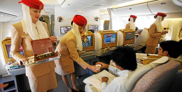 Flight attendants serve journalists during a flight tour organized by Emirates airline in Dubai September 7, 2007. Emirates, the largest Arab airline, may decide as early as next month on a 50-plane order between Boeing 787 aircraft and Airbus A350, and take an option for 50 more, its president Tim
