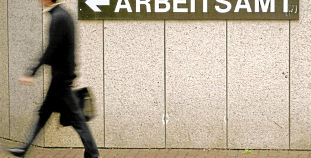 A man walks past a sign of a labour office in the western German city of Cologne September 4, 2003. Germany's seasonally-adjusted jobless total steadied in August, helped by labour market reforms, but the outlook for jobs remained weak. The Federal Labour Office said on Thursday unemployment adjuste