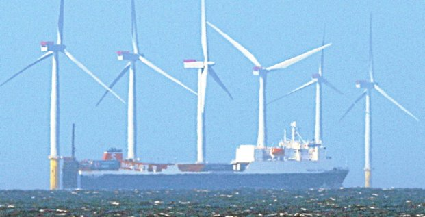 A ship sails past the Barrow offshore 90 megawatt wind farm, developed by British and Danish energy groups Centrica and DONG Energy, off the coast of Cumbria, England April 12, 2011. Offshore wind farm construction costs in Britain need to drop by around 30 percent over the next decade if the sector