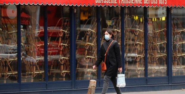 France / coronavirus / confinement : une femme portant un masque passe devant un restaurant fermé à Paris le 25 novembre 2020