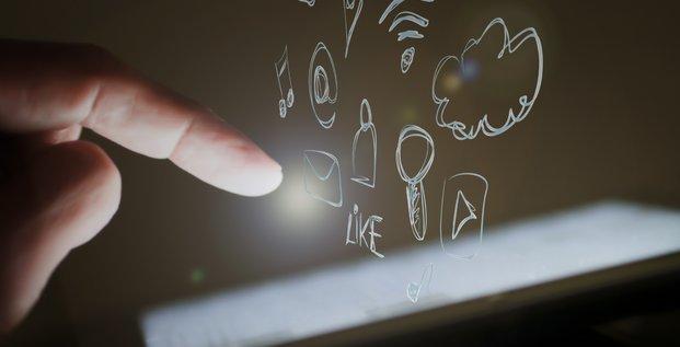 Nuage d'applications devant un iPad d'Apple (tablettes, apps, applis, Cloud, touch écran, smartphone, écran tactile)