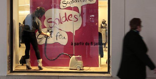 France, janvier 2016, une employée passe l'aspirateur sur un panneau Soldes dans la vitrine d'une boutique