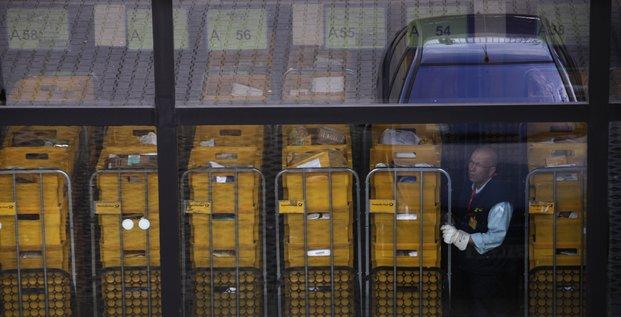 Un homme regarde à travers une fenêtre dans un centre international de tri postal à l'aéroport de Frankfort en septembre 2009 (colis, courrier)