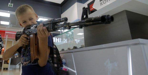 Un enfant tient un faux AK-47 de Kalachnikov dans une boutique souvenirs à l'aéroport de Moscou