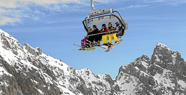 Skiers and snowboarder sitting in a chairlift in front of the Alps during the 2010/2011 winter season opening day at Germany's highest mountain Zugspitze near Garmisch-Partenkirchen October 30, 2010.    REUTERS/Michaela Rehle (GERMANY - Tags: ENVIRONMENT SOCIETY)