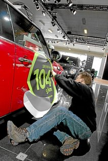 A man flattens down a sticker indicating the fuel consumption and CO2 emission rate of a Mini car during preparations for the 87th European Motor Show Brussels 2009 January 15, 2009. The car show will be inaugurated on Friday.  REUTERS/Sebastien Pirlet   (BELGIUM)