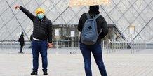 Coronavirus : un touriste portant un masque est photographié devant le Louvre, à Paris, le 14 mars 2020