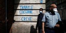 Coronavirus : deux personnes portant un masque passent devant un slogan disant : Travaille, consomme, crève (à Paris)