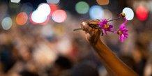 Violences policières États-Unis : une personne brandit une fleur, tandis que les manifestants s'assoient en silence pendant neuf minutes dans le cadre d'une manifestation pacifique pour protester contre la mort de George Floyd