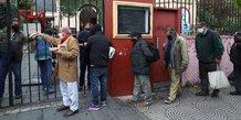 Buenos Aires, Argentine : des gens font la queue pour recevoir une portion de ragoût à la soupe populaire organisée à l'église Caacupe, le 23 juillet 2020