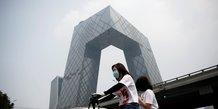 Chine : une femme portant un masque roule en vélo électrique devant le siège de la Télévision centrale de Chine à Pékin le 16 juillet 2020