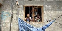 Yémen : des enfants de la communauté Muhamasheen regardent depuis la fenêtre de leur maison à Sanaa