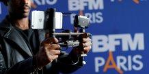 Un journaliste de BFM Paris tient un iPhone pour filmer lors d'une conférence de presse en octobre